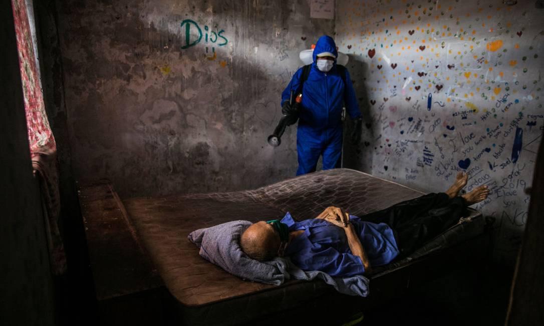 Profissional de saúde peruano desinfecta quarto onde um homem morreu por Covid-19 Foto: Anadolu Agency / Anadolu Agency via Getty Images
