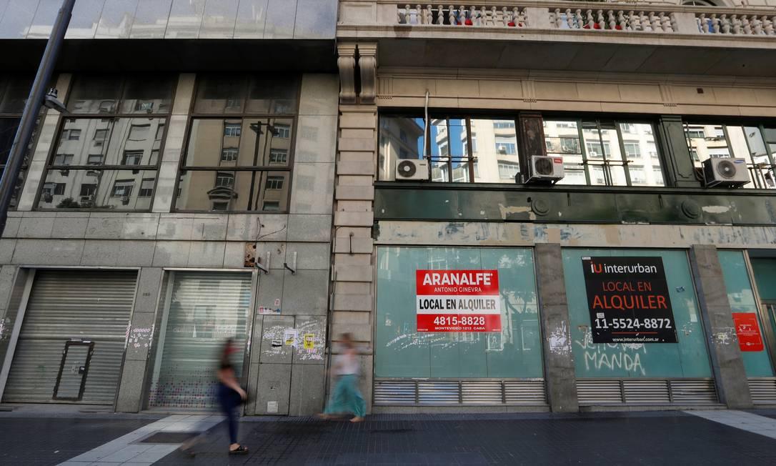 Pedestres passam em frente a lojas fechadas no Centro de Buenos Aires; crise econômica agravada pela pandemia impõe opções difíceis Foto: AGUSTIN MARCARIAN / REUTERS