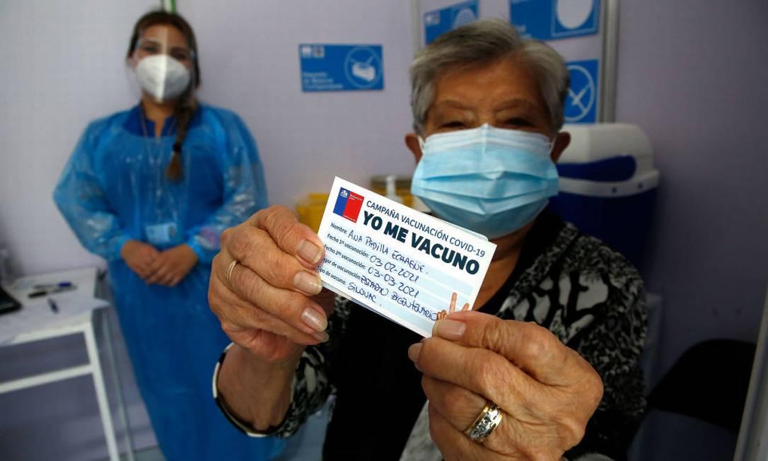 Idosa chilena mostra o cartão de vacinação contra Covid-19 Foto: Marcelo Hernandez / Getty Images