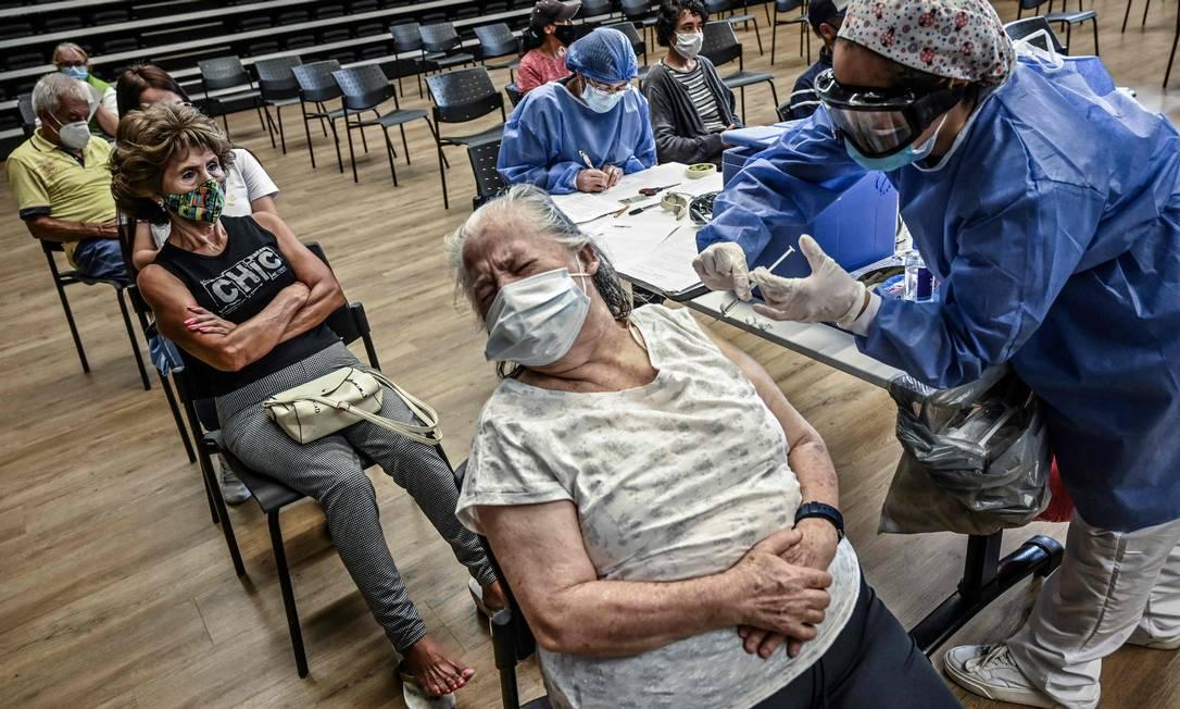 Mulher idosa é vacinada em um centro de vacinação, em Medellín, Colômbia. O presidente colombiano Ivan Duque reforçou no domingo o toque de recolher imposto nas cidades com a maior ocupação hospitalar para conter uma nova onda de infecções e mortes por Covid-19 Foto: JOAQUIN SARMIENTO / AFP