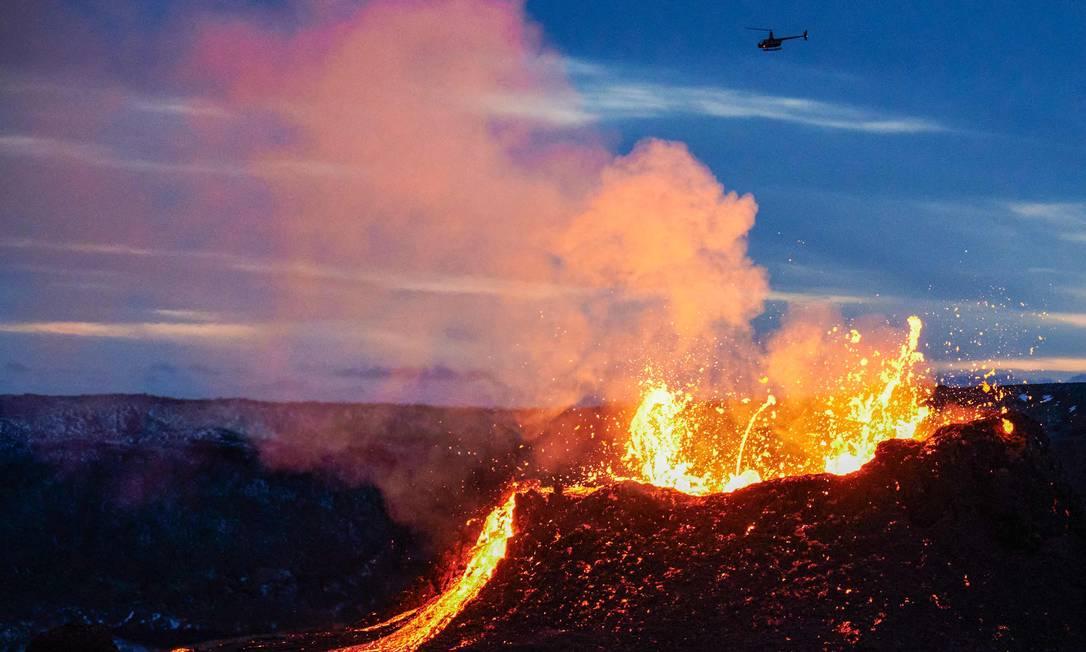 Helicóptero voa de uma fissura perto de Fagradalsfjall na Península de Reykjanes, na Islândia. A erupção vulcânica, já acontece há mais de duas semanas na Islândia, a cerca de 40 quilômetros de Reykjavik Foto: HALLDOR KOLBEINS / AFP