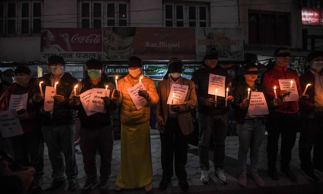 Ativistas de direitos humanos seguram velas durante um protesto contra o golpe militar de Mianmar, em Kathmandu, Nepal Foto: PRAKASH MATHEMA / AFP