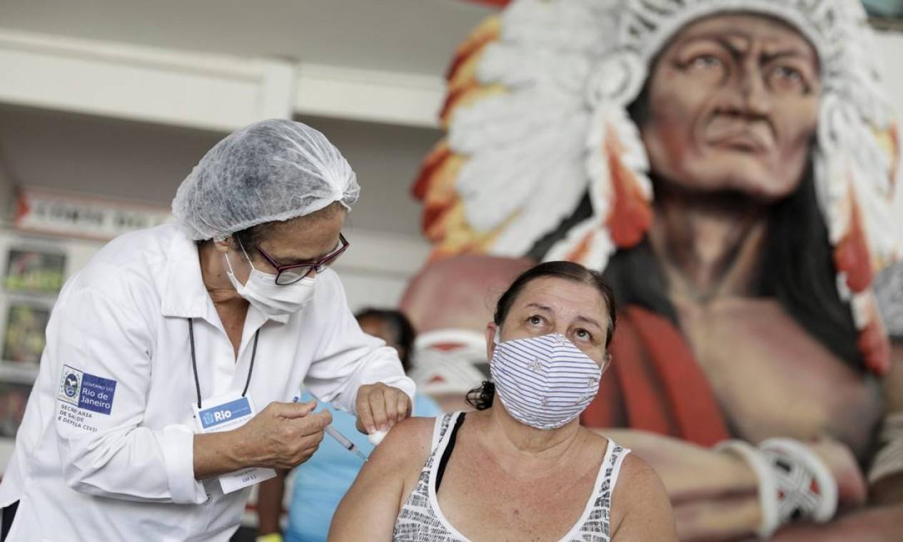 Mulher recebe vacina Coronavac contra o novo coronavírus na sede do Cacique de Ramos, um dos blocos carnavalescos mais tradicionais do Rio de Janeiro Foto: RICARDO MORAES / REUTERS