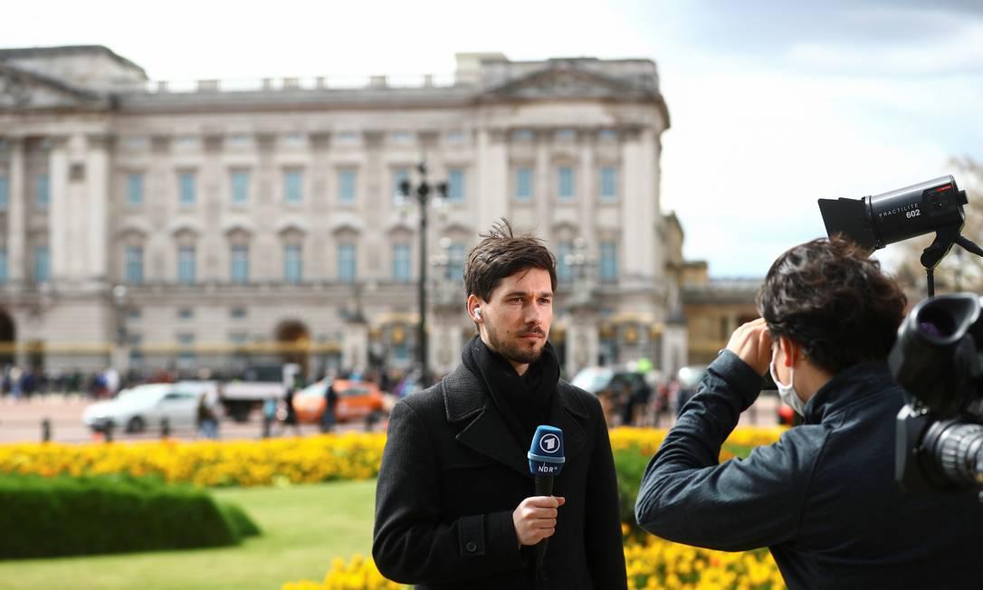 Jornalistas noticiam a morte do príncipe Philip, em frente ao Palácio de Buckingham depois do anúncio oficial da monarquia Foto: HANNAH MCKAY / REUTERS