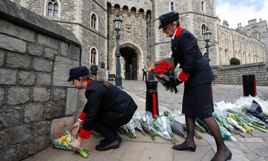 Funcionários do castelo de Windsor recolhem flores deixadas para o príncipe Philip Foto: PETER NICHOLLS / REUTERS