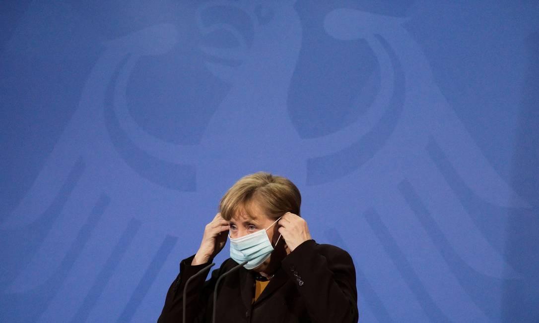 Chanceler alemã Angela Merkel coloca máscara durante entrevista coletiva no dia 30 de março Foto: POOL / REUTERS
