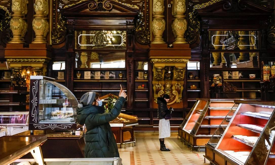 Cliente fotografa o interior da Yeliseyevsky, onde já se vê prateleiras e mostradores vazios Foto: MAXIM SHEMETOV / REUTERS