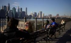 Sentados em bancos no Brooklyn, americanos conversam com os arranha-céus de Manhattan ao fundo; Nova York vê aumento dos casos Foto: ED JONES / AFP/7-4-21