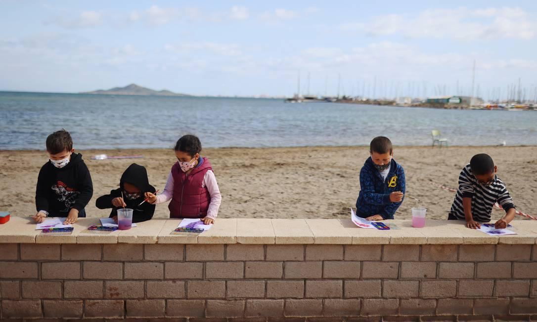Alunos da escola pintam durante uma aula ministrada ao ar livre em praia da espanha Foto: NACHO DOCE / REUTERS