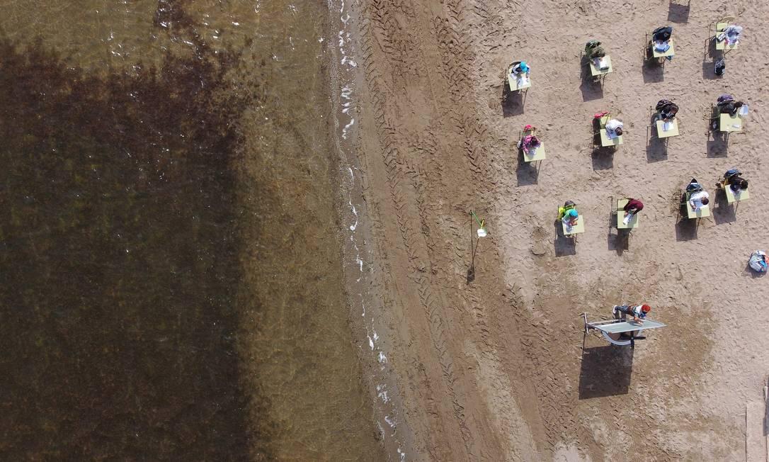 Imagem aérea mostra alunos da escola durante aula à beira-mar Foto: NACHO DOCE / REUTERS