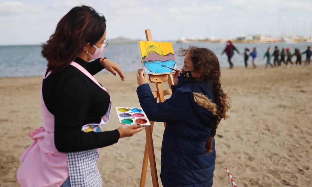Professora orienta aluna durante ao de arte em praia no sul da Espanha Foto: NACHO DOCE / REUTERS