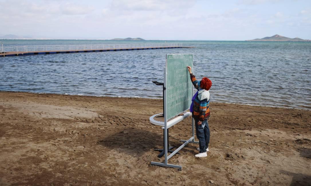 Um professor escreve em um quadro de giz enquanto dá aula para os alunos na Praia dos Netos, perto de Cartagena, sul da Espanha Foto: NACHO DOCE / REUTERS