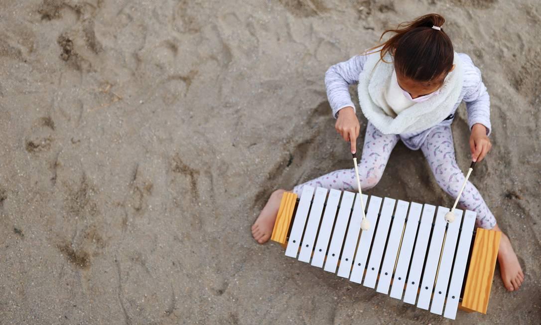Uma aluna toca xilofone durante uma aula do projeto Foto: NACHO DOCE / REUTERS