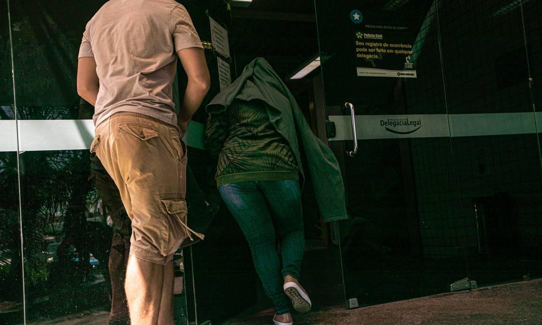 Com o rosto coberto, Thayna de Oliveira Ferreira chega para depoir na 16ª DP Foto: Brenno Carvalho / Agência O Globo