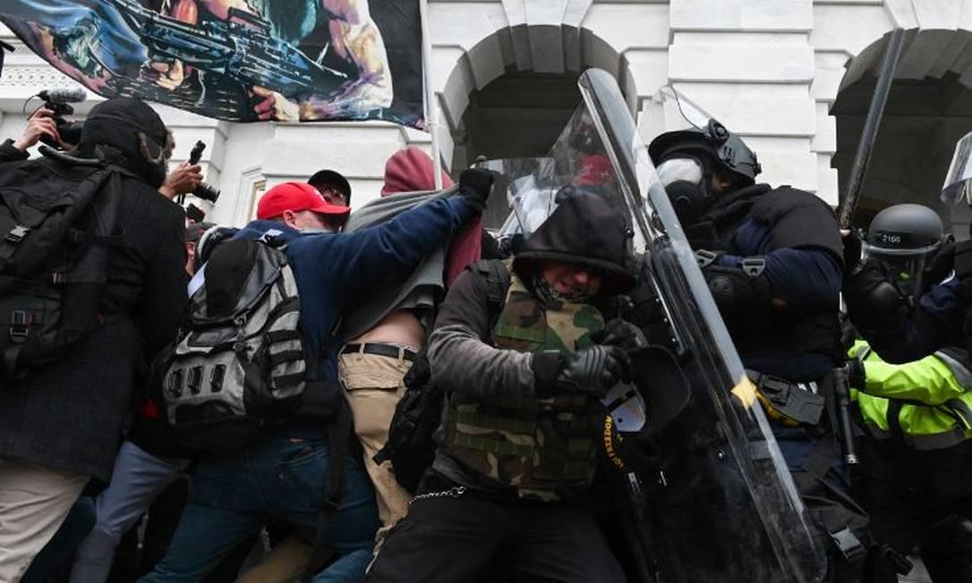 Polícia enfrenta invasores extremistas pró-Trump no Capitólio durante conflito em 6 de janeiro de 2021 Foto: ROBERTO SCHMIDT / AFP