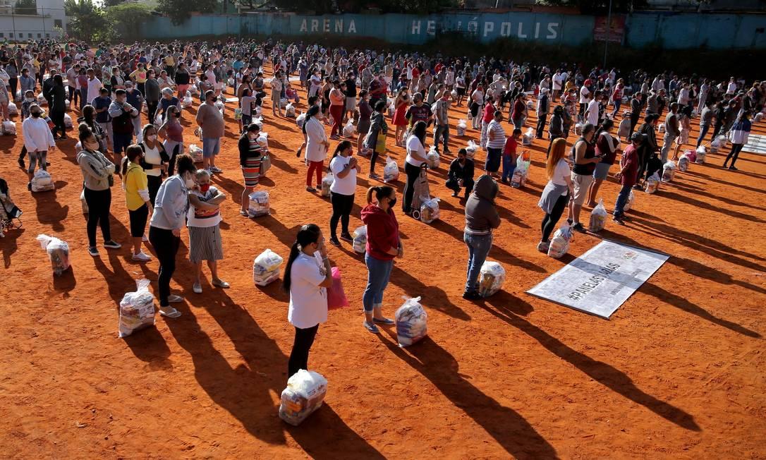Grupo distribuiu nesta quarta-feira (14) cestas para brasileiros que esperavam em longas filas, mantendo distância social, na favela Heliópolis, São Paulo Foto: CARLA CARNIEL / REUTERS
