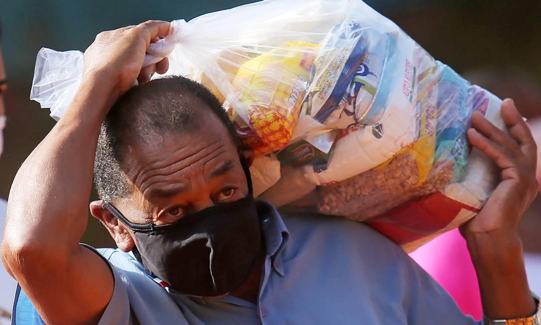 Homem carrega uma cesta básica entregue pelo G-10 Favelas, grupo formado por empresários que vem ajudando no combate á fome em favelas da cidade de São Paulo Foto: CARLA CARNIEL / REUTERS
