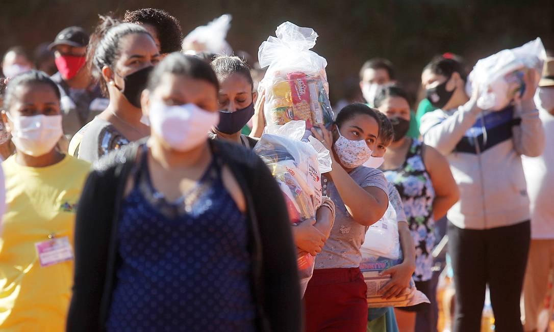 Pessoas carregam cestas básicas distribuídas por grupo de empresários para moradores de comunidades da capital paulista. Brasil tornou-se um dos países mais afetados pela pandemia no mundo, com cerca de 4.000 pessoas morrendo por dia de Covid-19 Foto: CARLA CARNIEL / REUTERS