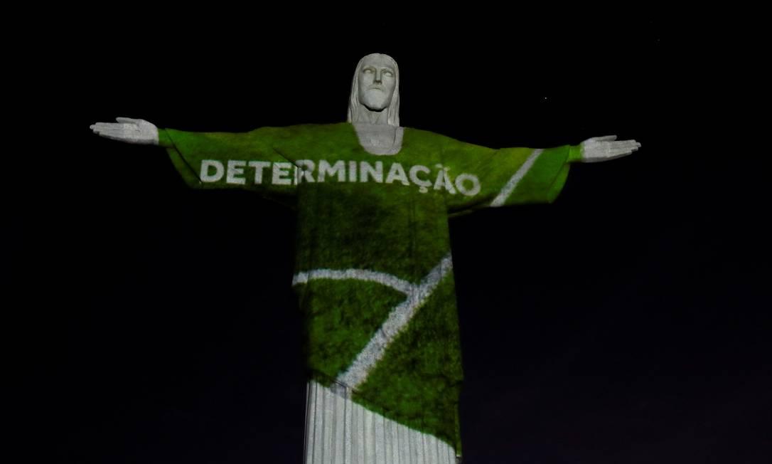 """Monumento ganhou iluminação especial para marcar os 100 dias para as Olimpíadas de Tóquio. Palavras inspiradoras, como """"determinação"""", """"respeito"""" e """"coragem"""" também foram projetadas na estátua símbolo do Rio Foto: RICARDO MORAES / REUTERS"""