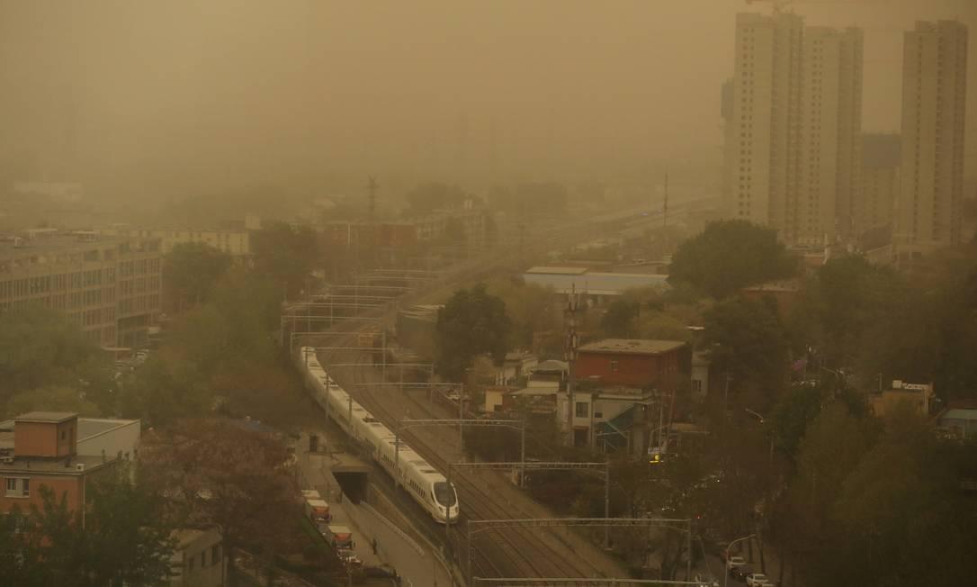 Trem de alta velocidade passa por prédios envoltos em areia e poeira em meio a uma tempestade de poeira em Pequim, China Foto: TINGSHU WANG / REUTERS