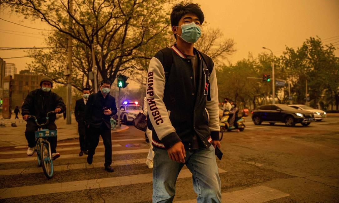 Pessoas atravessam uma rua durante uma tempestade de areia em Pequim Foto: NICOLAS ASFOURI / AFP