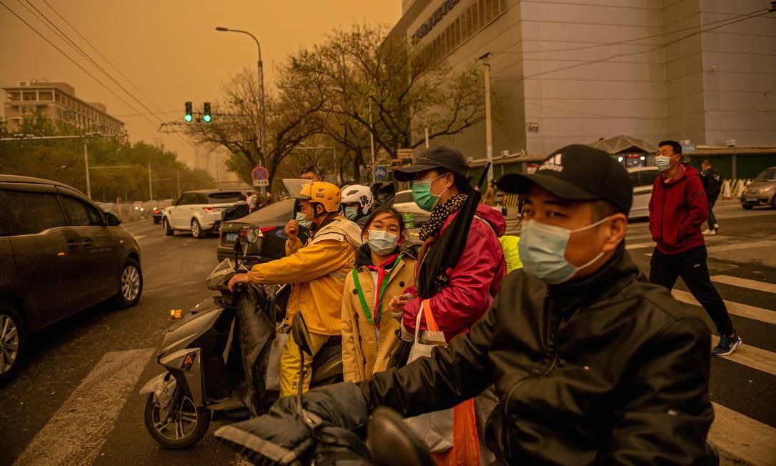 Pessoas esperam para atravessar uma rua durante uma tempestade de areia em Pequim Foto: NICOLAS ASFOURI / AFP