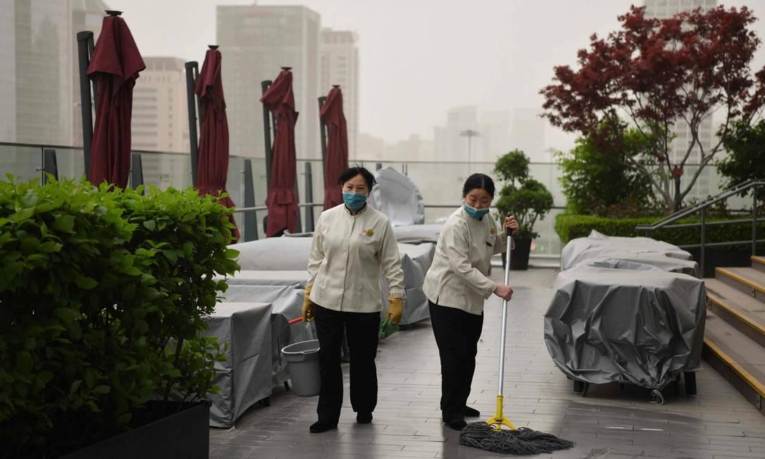 Dois trabalhadores varrem o chão de um restaurante ao ar livre no distrito comercial central Foto: GREG BAKER / AFP
