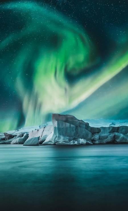Luzes da aurora boreal fotografadas a partir da lagoa de uma geleira na Islândia, por Tom Kahler Foto: Tom Kahler / Shackleton/Divulgação