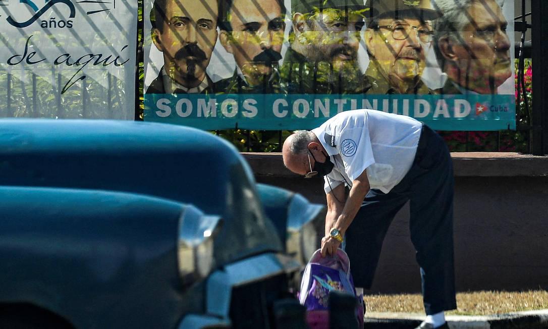 Cubano passa por cartaz com imagens de revolucionários, passando pelos irmãos Castro e o presidente Díaz-Canel Foto: YAMIL LAGE / AFP