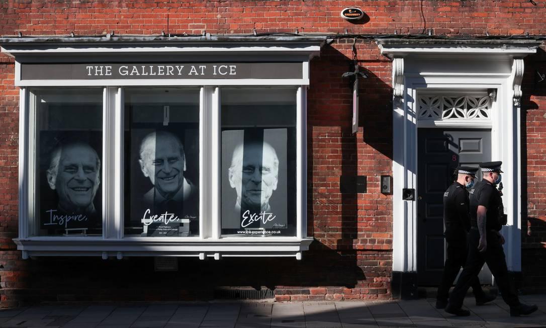 Policiais passam por uma vitrine com fotos do príncipe Philip, marido da Rainha Elizabeth, em Windsor, perto de Londres Foto: HANNAH MCKAY / REUTERS
