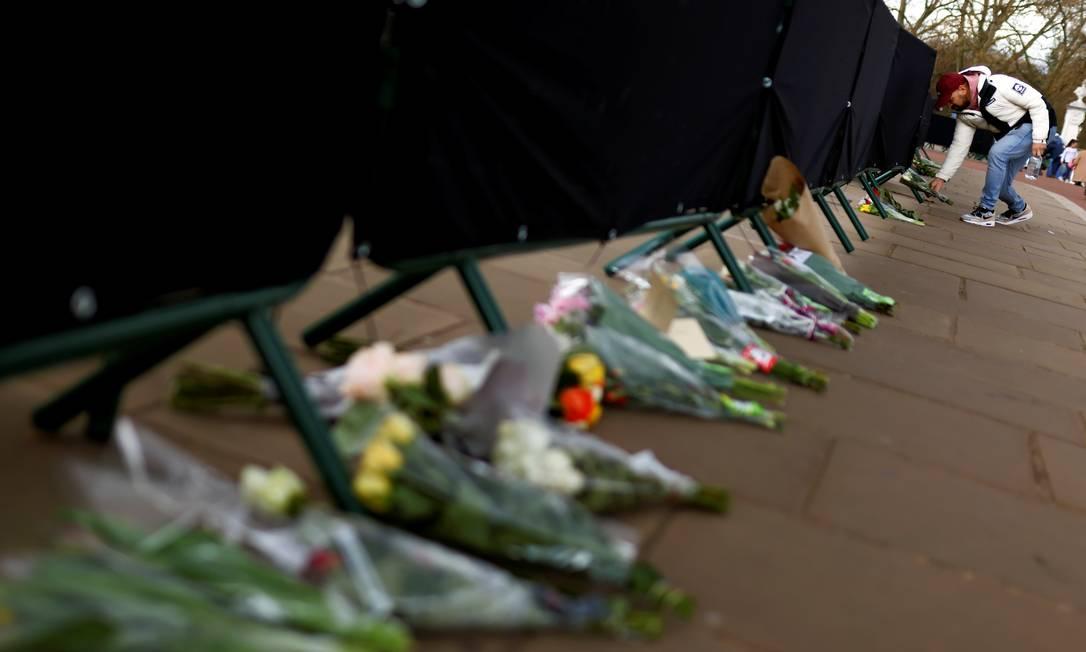 Um homem coloca flores em frente ao Palácio de Buckingham Foto: TOM NICHOLSON / REUTERS