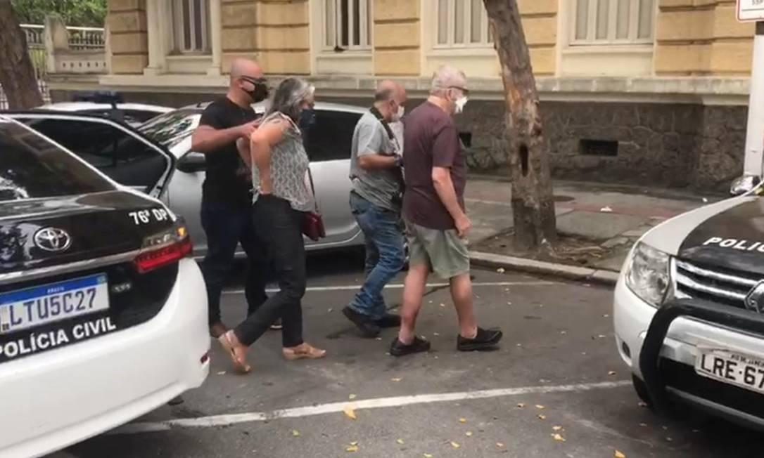 O casal (ele de camisa roxa, ela de blusa cinza) é conduzido pelos policiais após a prisão Foto: Reprodução