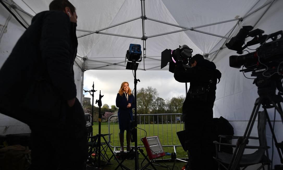 A repórter da CNN grava uma matéria em uma tenda de mídia temporária instalada no Castelo de Windsor na véspera do funeral do príncipe britânico Foto: BEN STANSALL / AFP