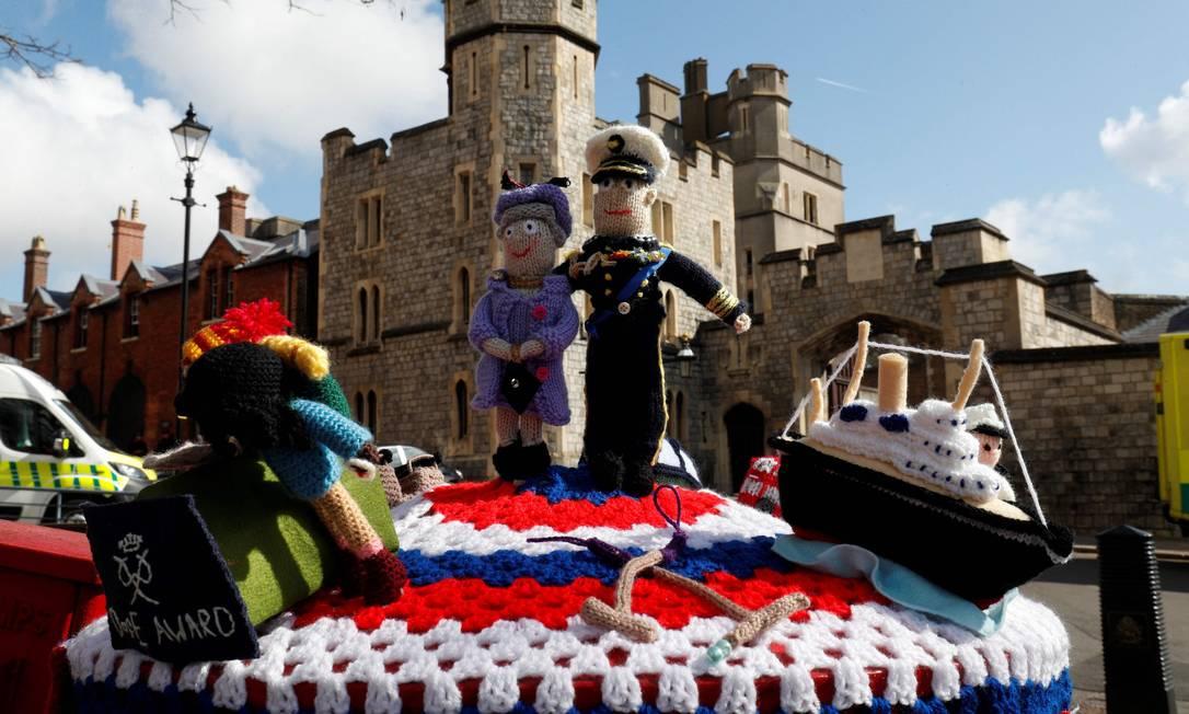 Bonecos tricotados representando a rainha Elizabeth II e o príncipe Philip são vistos sobre uma caixa de correio perto do Castelo de Windsor Foto: ADRIAN DENNIS / AFP