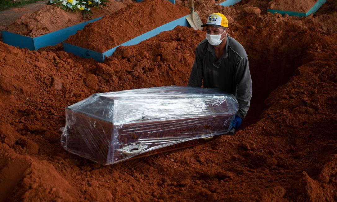 Coveiro abaixa o caixão de uma vítima de Covid-19 no cemitério de Nossa Senhora Aparecida, em Manaus, no Amazonas. O Brasil, com 212 milhões de habitantes, tem um total de mortos de mais de 360 mil pela doença, perdendo apenas para os Estados Unidos Foto: MICHAEL DANTAS / AFP