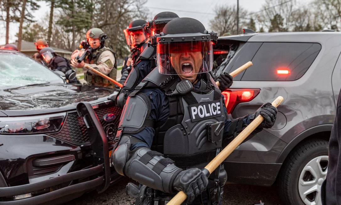 Policiais se protegem enquanto enfrentam manifestantes depois que uma policial atirou e matou um jovem negro no Brooklyn Center, Minneapolis, Minnesota Foto: KEREM YUCEL / AFP