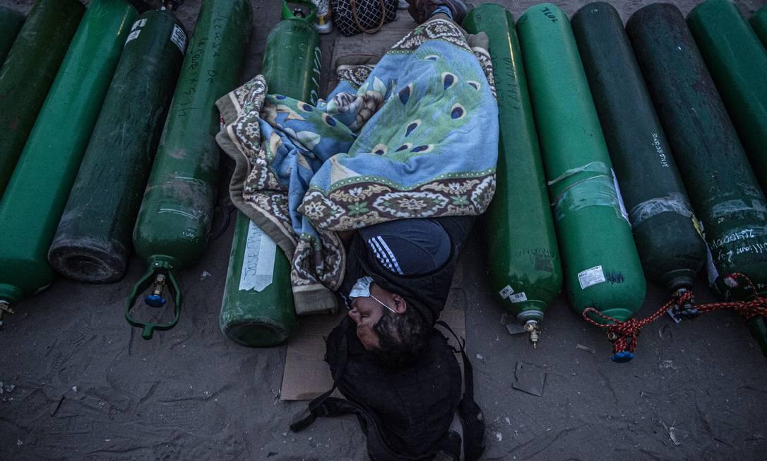 Uma pessoa dorme ao lado de cilindros de oxigênio vazios enquanto espera para reabastecê-los em Villa El Salvador, na periferia ao sul de Lima, no Peru Foto: ERNESTO BENAVIDES / AFP