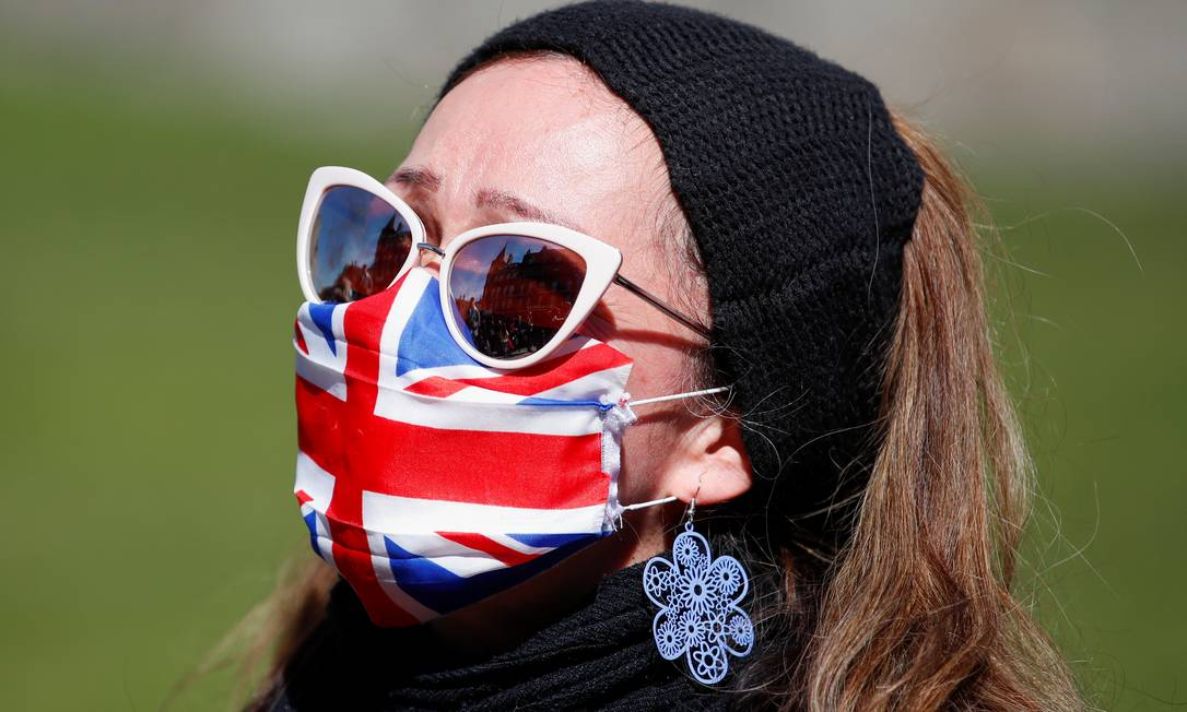 Mulher usando uma máscara facial Union Jack está do lado de fora do Castelo de Windsor durante o funeral do príncipe Philip da Grã-Bretanha, em Windsor Foto: PETER CZIBORRA / REUTERS