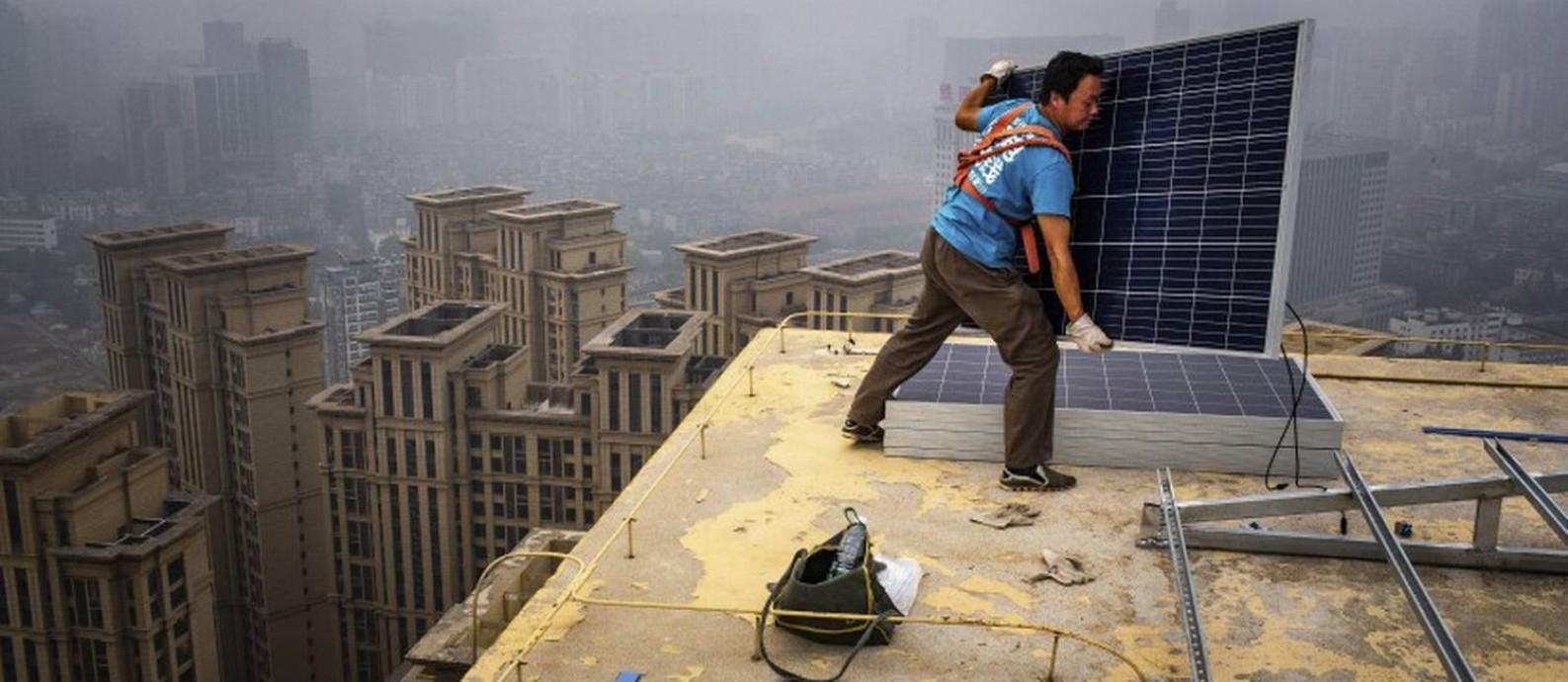 Homem instala painéis solares no topo de um edifício de 47 andares em Wuhan, na China; país fabrica 60% dos dispositivos do tipo no mundo Foto: BRYAN DENTON / NYT/5-7-18