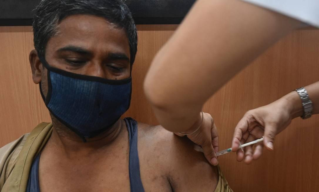 Profisisonal de saúde é vacinado contra a Covid-19 na Índia Foto: INDRANIL MUKHERJEE / AFP