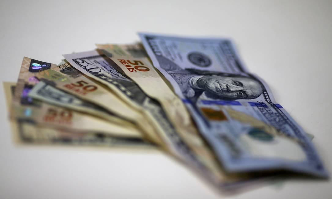 Cédulas de real e dólar: moeda americana está em queda no mundo, mas não no Brasil Foto: Ricardo Moraes / REUTERS