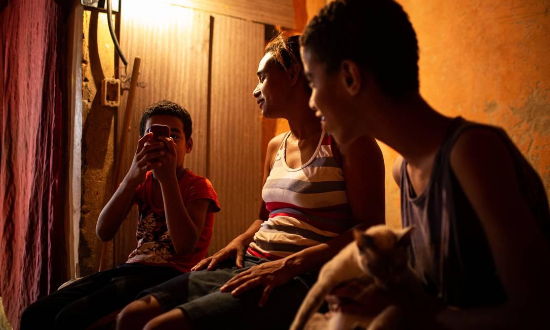 Cátia Telles do Couto com os filhos, João Victor, de 12 anos, e Miguel, de 9; sem atendimento especializado, os meninos ainda não aprenderam a ler e escrever Foto: Hermes de Paula / Agência O Globo