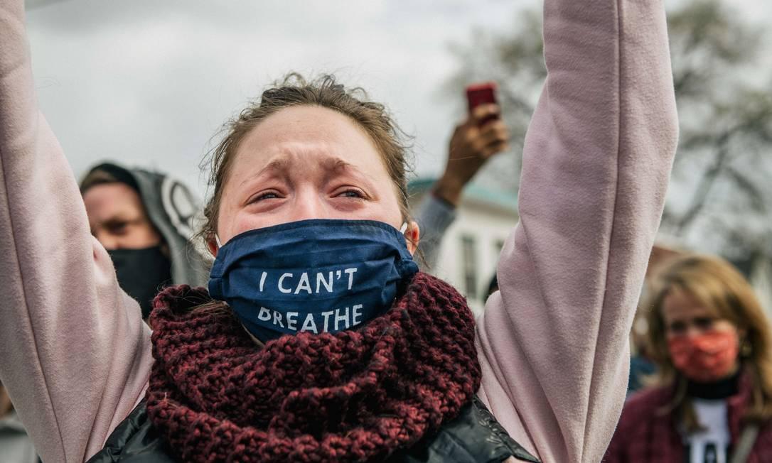 """Mmulher chora depois de ouvir o veredicto no cruzamento da 38th Street com a Chicago Avenu, em Minneapolis, Minnesota. Na máscara de proteção, a frase """"eu não consigo respirar"""", emblemarica frase dita por Floyd enquanto era asfixiado por Derek Chauvin Foto: Brandon Bell / AFP"""