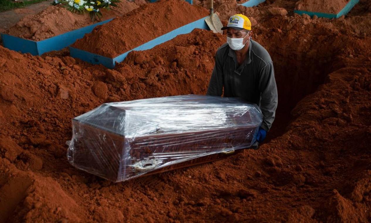 Funcionário de cemitério abaixa o caixão de uma vítima da COVID-19 no cemitério de Nossa Senhora Aparecida, em Manaus Foto: MICHAEL DANTAS / AFP - 15/04/2021