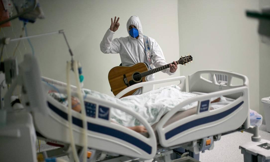 Profissional de saúde do hospital de caridade português em Belém, no Pará, canta e ora por um paciente com COVID-19 dentro das enfermarias do hospital e áreas de UTI Foto: TARSO SARRAF / AFP - 04/04/2021