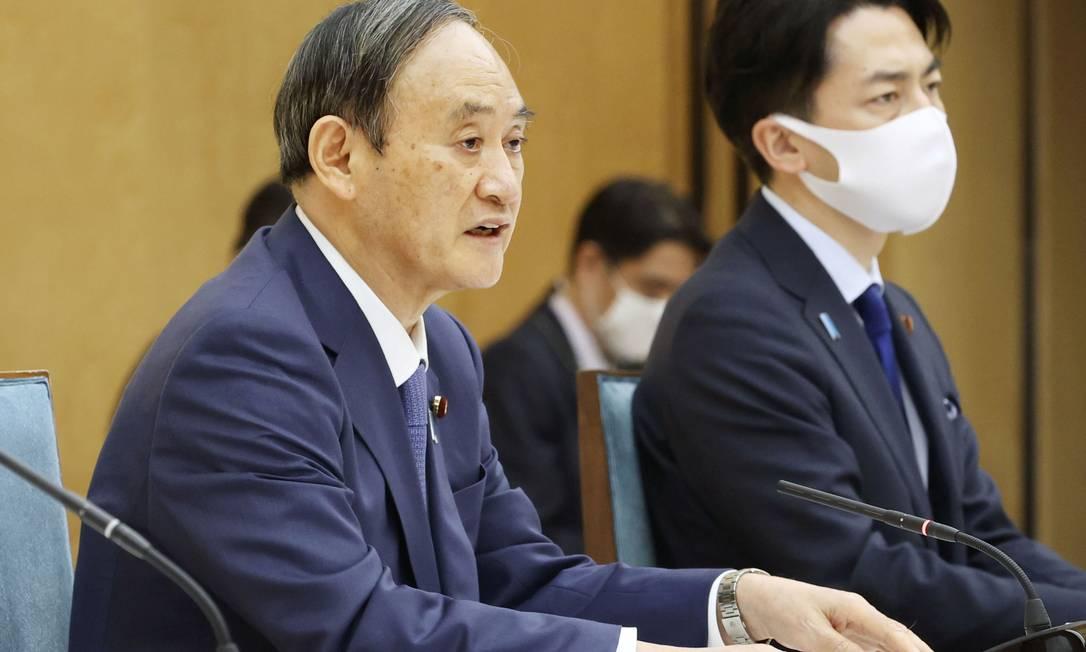 Primeiro-ministro do Japão, Yoshihide Suga, acompanhado pelo ministro do Meio Ambiente Shinjiro Koizumi, falou de parceria com os EUA para emissão zero Foto: KYODO / via REUTERS