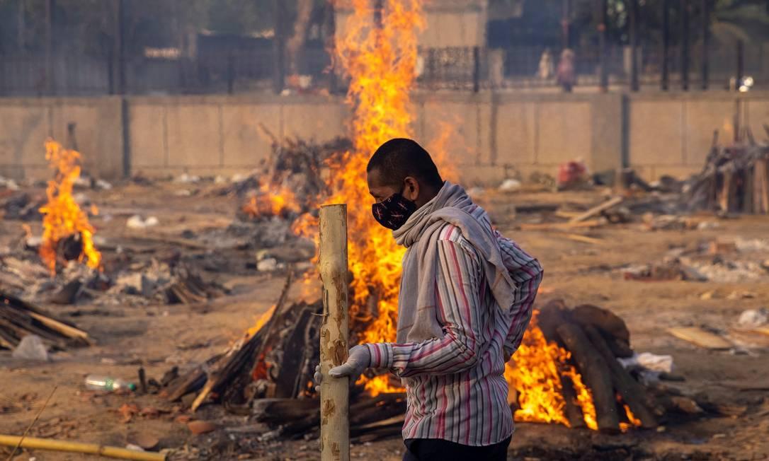 Homem passa por piras em um crematório em Nova Delhi, Índia Foto: Danish Siddiqui / REUTERS