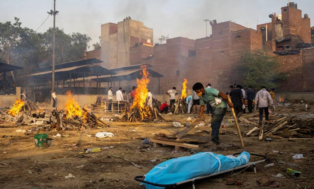 Um homem prepara fogueira para cremar o corpo de vítima da COVID-19, em um crematório em Nova Delhi, Índia Foto: Danish Siddiqui / REUTERS