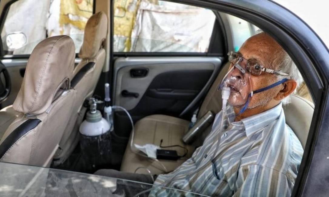 Sushil Kumar Srivastava foi fotografado sentado em seu carro, amarrado a um cilindro de oxigênio na cidade de Lucknow Foto: SUMIT KUMAR