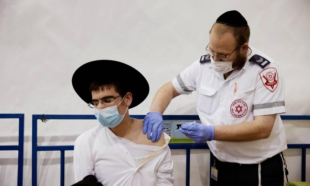 Judeu ultra-ortodoxo é vacinado contra a Covid-19, em Israel: país não teve nenhuma morte pela doença na sexta-feira Foto: RONEN ZVULUN / REUTERS